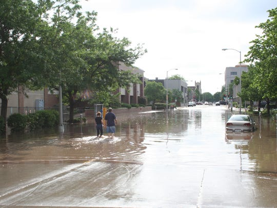 People wade through the flood waters on West Second Street, just feet away from former location of the Fond du Lac Reporter on Macy Street.
