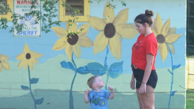 Cayson Soler, 2, looks up at Hannah Backhus, 17, while playing at the Rose Walter Park in Brookville on Sunday evening.
