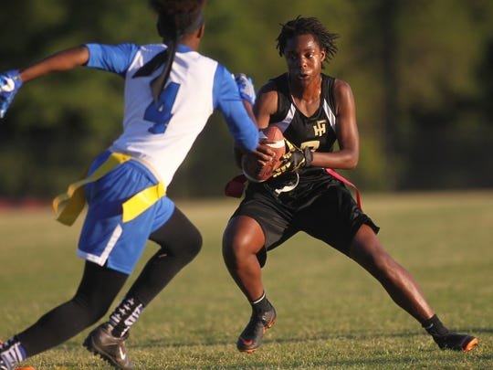 Florida High quarterback Janae Scott plants her foot in the ground to evade Godby defenders.