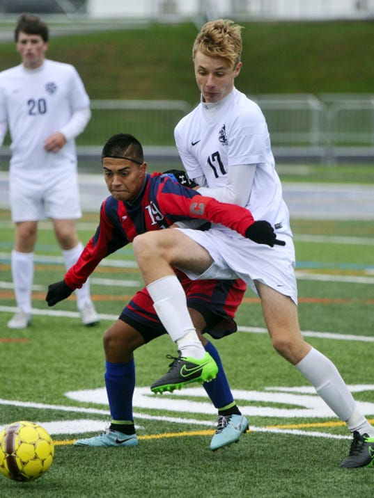 New Oxford's Luis Partida, left, and Dallastown's Jake Marsico battle for the ball during the Wildcats' 2-0 victory on Saturday.
