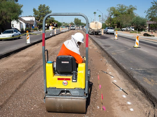 The middle of Thomas Road near 75th Street is getting a makeover as Silverico Lopez compacts gravel.