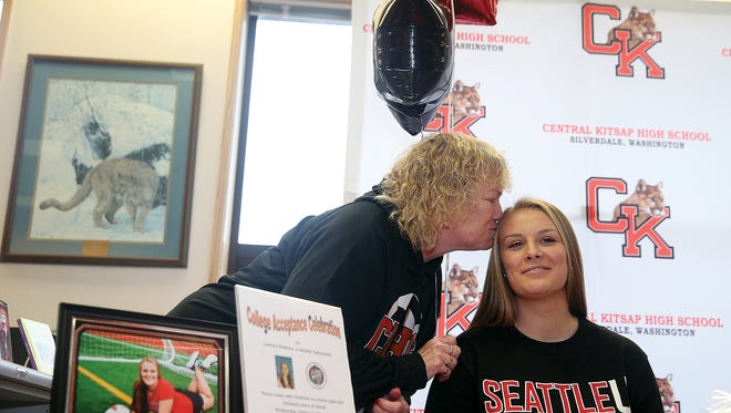 Central Kitsap's girls soccer coach Vicky Webb gives a kiss to player Lauren Hudson during her signing day ceremony earlier this month. Webb is retiring after 17 seasons coaching the Cougars. Central Kitsap boys coach Keith Sargent will now lead both programs.