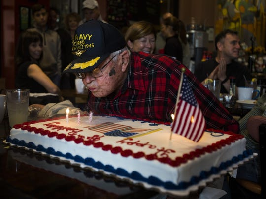 Robert Reed, a World War II U.S. Navy veteran, blows the candles out on his surprise birthday cake at EJ's Bayfront Cafe on Saturday in East Naples.
