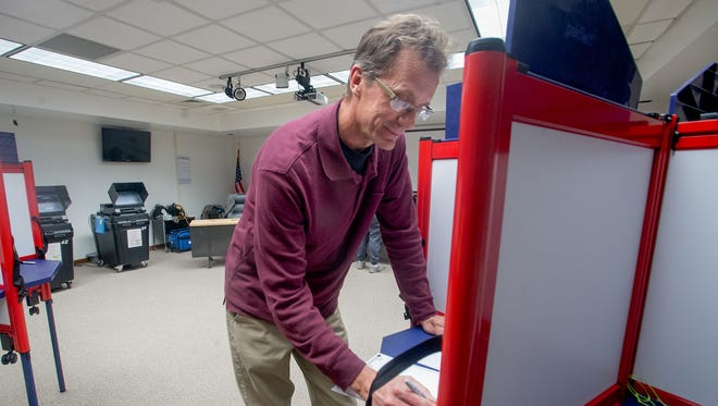 Voter Paul Pavlik fills in his ballot Tuesday at a polling station at the Farmington Municipal School District offices.