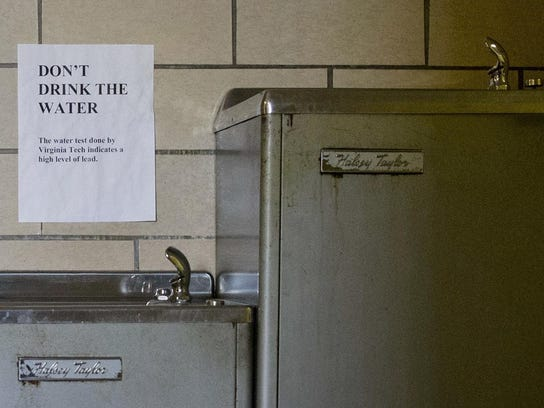 In this 2016 photo, signs warn people not to drink the lead-contaminated water from a water fountain at Woodside Church in Flint, Mich.