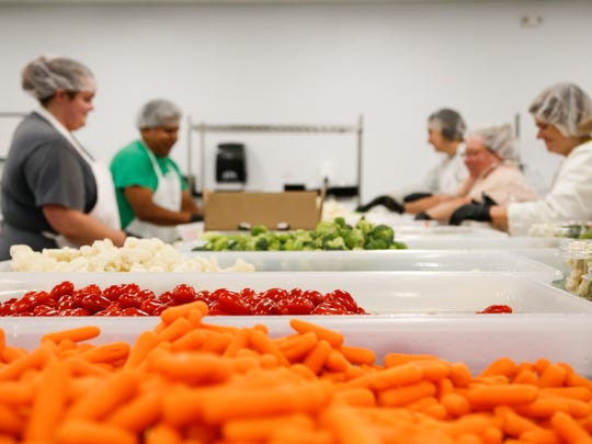 Employees at Round Lake Produce & Distributing in DeWitt Township prepare vegetable trays Wednesday, Sept. 13, 2017.  The company has about 45 employees.