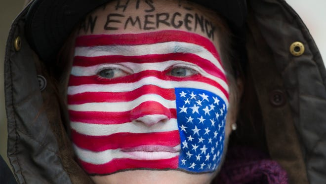 Courtney Nuding has her face painted with an upside down American Flag as she protests outside the offices of Senators Lamar Alexander and Bob Corker to protest Donald Trump's executive order banning immigration from certain countries Sunday Jan. 29, 2017, in Nashville, Tenn.