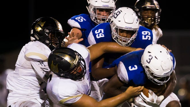 Community School of Naples senior, Tay Williams, right, charges through defenders on Friday, September 22, 2017 at Community School of Naples during the game against Moore Haven High School.