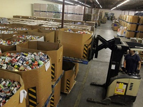 A worker operates a fork lift while loading cans of food at the Harry Chapin Food Bank warehouse on Fowler Street