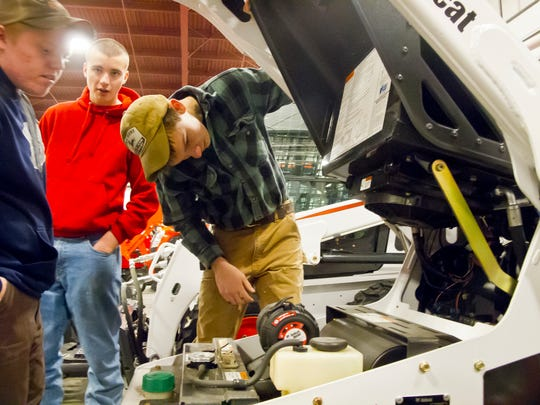 Bennett Cochran, 17, at right, inspects the diesel powerplant of a Bobcat loader in the company of his Danville High School classmates.