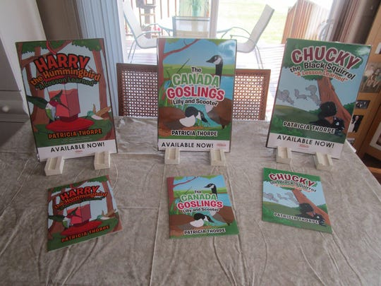 """Pictured are Thorpe's books """"Harry the Hummingbird,"""" """"The Canada Goslings: Lilly and Scooter,'"""" and """"Chucky the Black Squirrel."""""""