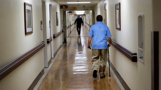 In this March 11, 2015 photo, a patient walks down a hallway at the Fayetteville Veterans Affairs Medical Center in Fayetteville, N.C. The VA hospital is one of the most backed-up facilities in the country.