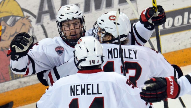 St. Cloud State's Joey Benik (facing) celebrates his goal and 100th career point with linemates David Morley and Patrick Newell on Saturday at AMSOIL Arena in Duluth. The Huskies beat Minnesota-Duluth 2-1 in two overtimes.