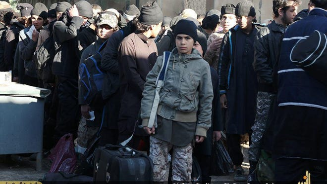 ADVANCE FOR USE SUNDAY, JULY 19, 2014 AT 1 P.M. EDT (17:00 GMT) AND THEREAFTER - In this photo released on Feb. 9, 2015, by a militant website, which has been verified and is consistent with other AP reporting, a boy in a military uniform, center, waits with other men to join training camps run by the Islamic State group, in Deir el-Zour, east Syria. (Militant website via AP)