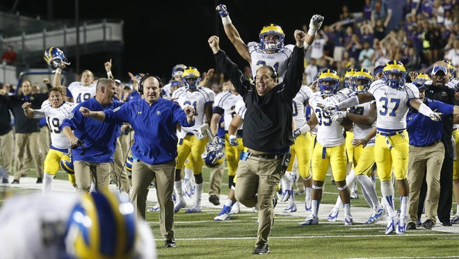 The Delaware bench, including leaping co-defensive coordinator Tim Weaver, celebrates after a fourth-down goal-line stop gave the Blue Hens a 30-23 overtime win at JMU in 2014.