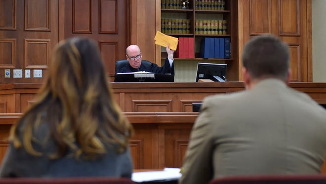 Door County Circuit Judge David Weber holds up victim impact letters addressed to him during the course of the theft case against former Door County Humane Society executive director Carrie Counihan, seated left, during his sentencing statement Friday. Counihan was sentenced to nine months in jail.