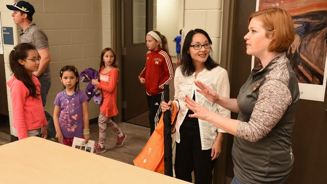 Pearson Elementary art teacher Victoria Hoover, right, greets Michelle Saucier, middle, and her kids Jasmine and Katelyn during the brand-new school's  open house.