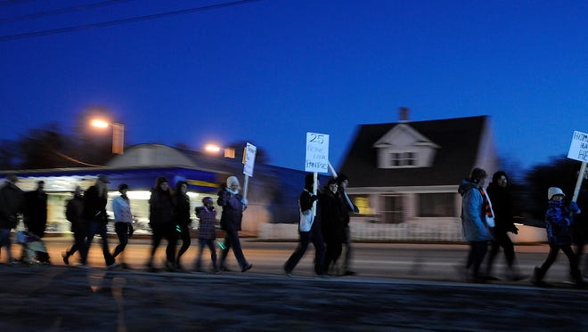 People carry signs to raise awareness about homelessness during a Hunger and Homelessness Awareness Week rally at Manna for Life in Green Bay on Tuesday, Nov. 13, 2012.