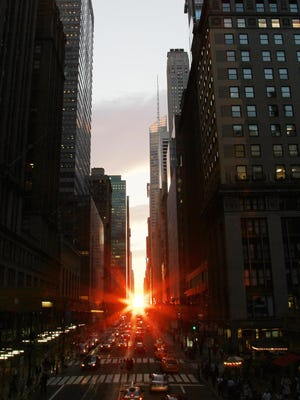 """AP Photo/Julio Cortez The sunset seen from 42nd Street during a phenomenon known as ?Manhattanhenge,? in New York City. The sun is seen as it sets between Manhattan buildings on 42nd Street during a phenomenon known as """"Manhattanhenge,"""" Wednesday, July 13, 2011 in New York City. Manhattanhenge, sometimes referred to as the Manhattan Solstice, happens when the setting sun aligns with the east-to-west streets of the main street grid. The term comes from Stonehenge, at which the sun aligns with the stones on the solstices in England. (AP Photo/Julio Cortez)"""