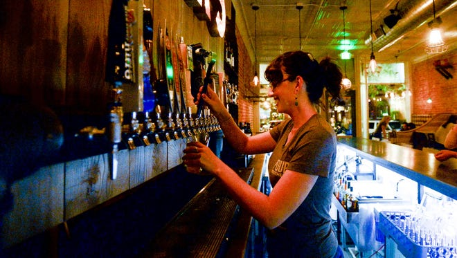 Madeline Barbour serves up drinks at Pour Brothers Friday, Oct. 3, 2014, in Fort Collins, CO.