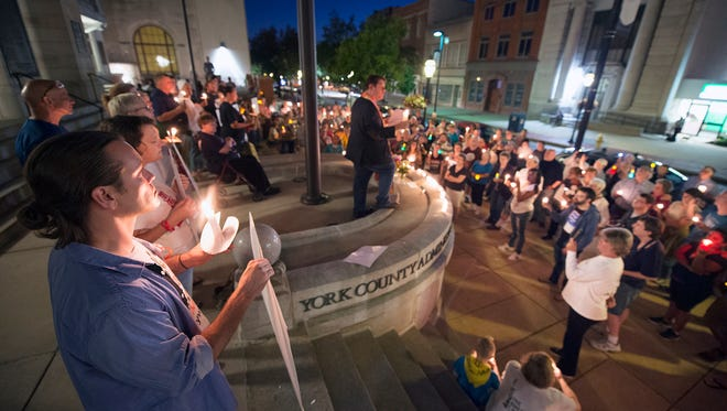Errol Wizda, of Camp Hill, left, and several hundred participants gathered in front of the York County Administrative Center Sunday night in response to events that unfolded when white supremacist groups gathered in Charlottesville, Virginia, on Saturday.