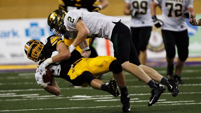 Bettendorf's Keaton Cain is tackled by Cedar Rapids, Kennedy's Shaun Beyer during their semifinal game at the UNI dome on Friday, November 13, 2015 in Cedar Falls.