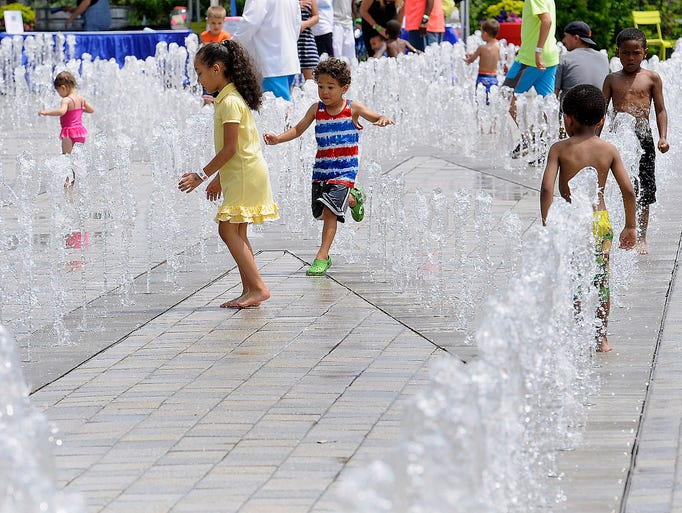 Children play in fountains of water during the 8th