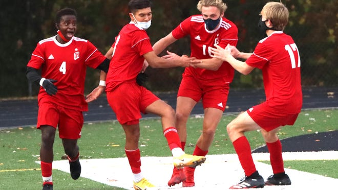 Abraham Arellano (center), celebrates a goal with teammates during the district semifinals against Zeeland East at Holland Christian.