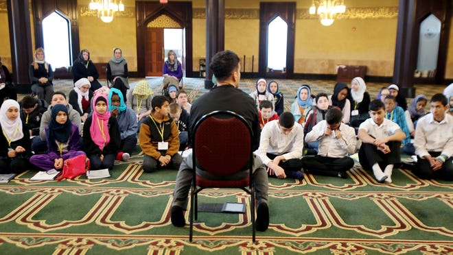 Brother Hussein Charara, seated, is leading a discussion about Islamic sacred text during a session of the Religious Diversity Journey program at the Islamic Center of America in Dearborn, where middle-school students are learning about Islam on Wednesday. The program exposes children to different religions.