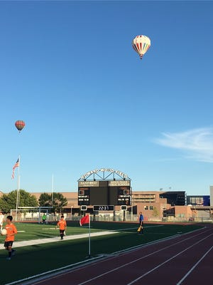 Hot-air balloons fly over Howard Wood Field during Tuesday's boys soccer game between Washington and Huron.