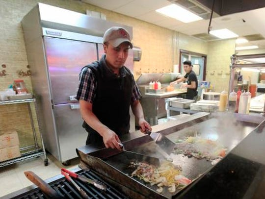 Cooks prepare stir fry at Yummy Buffet & Grill Sunday