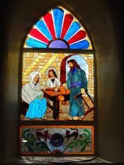 This July 21, 2016, photo provided by Carrie Leven, shows one of the stained glass windows made by volunteers for the historic San Antonio Catholic Church in Questa, N.M. The community will celebrate the rededication of the church with a special Mass on Sunday, Aug. 14, 2016. It took volunteers tens of thousands of hours over the last several years to rebuild the heart of one mountain village in northern New Mexico.