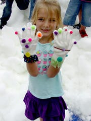 A child shows off her gloves while playing in the snow.