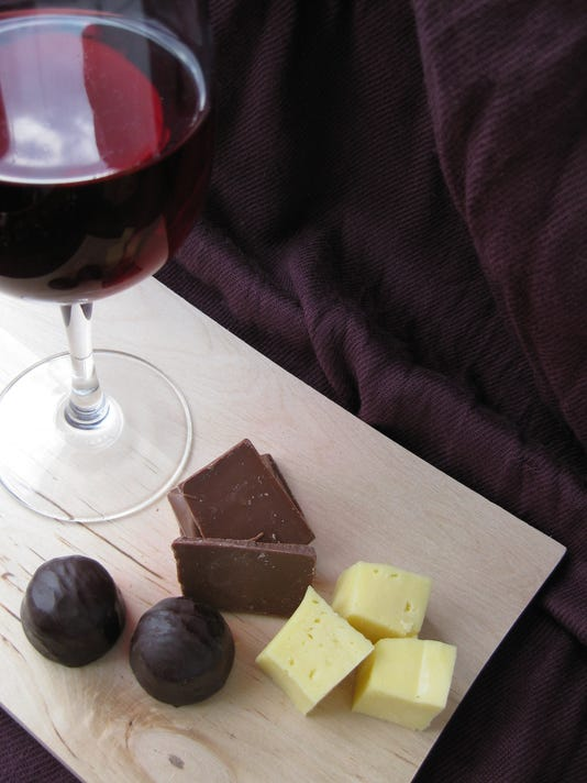 Glass of wine next to pieces of chocolate and cheese