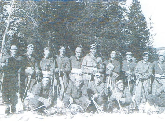 """Soldiers pose for a group photo at the 10th Mountain Training Center. Soldiers are on skis with rifles slung over their backs. Pvt. Delmas """"Dev"""" Devenger of Danville is front row second from left. He later died while fighting in Italy."""