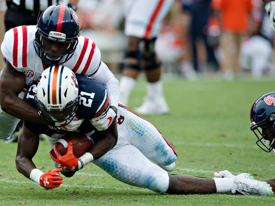 Auburn running back Kerryon Johnson (21) is tackled by Ole Miss defensive back C.J. Miller (8) during the NCAA football game between Auburn and Ole Miss on Saturday, Oct. 7, 2017, in Auburn, Ala.