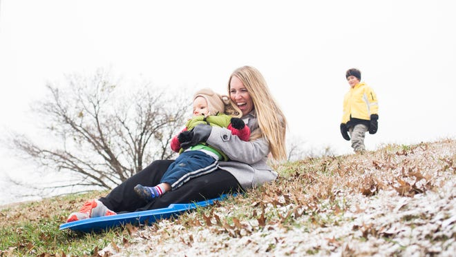 Ruthanne Saunders sleds with her son Abraham Saunders, 1, at McCants Middle School on Saturday in Anderson.