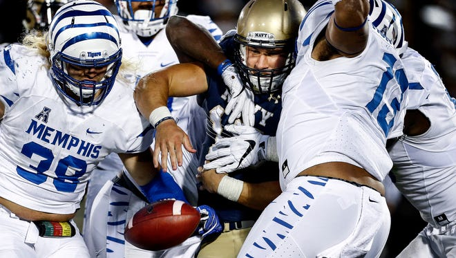 Navy quarterback Will Worth (middle) loses control of the ball while being gang tackled by the University of Memphis defense during third quarter action at Navy-Marine Corps Memorial Stadium in Annapolis, Maryland. Worth was called down on the play as Navy retains possession of the ball.