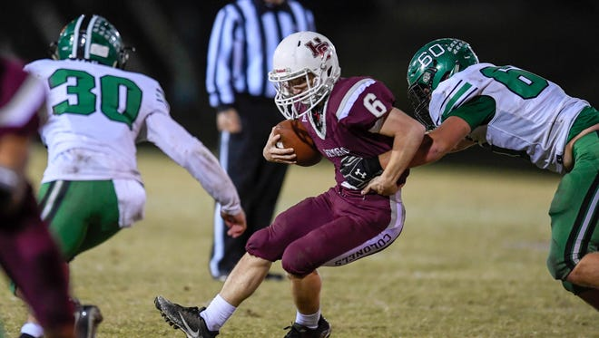 Hendeson's Logan Green (6) rushes against defense from Meade's Bryce Dawson (30) and Shawn DeRossett (60) during Henderson's 21-14 win as Henderson County hosts Meade County in the first round of the playoffs at Colonel field Friday, November 3, 2017.