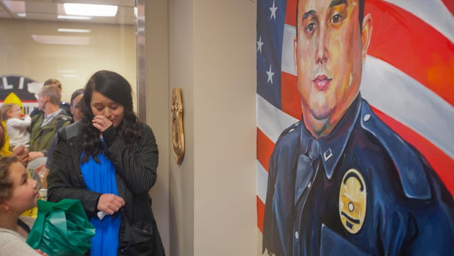 Ashley Rodman, wife of LMPD Officer Nicholas Rodman, who was killed in the line of duty in March 2017, weeps at the unveiling of his painting on the entrance wall of the 1st Division headquarters on 29th Street.Mar. 29, 2018