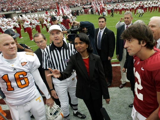 Secretary of State Condoleezza Rice, center, tosses the coin between Tennessee's Rick Clausen, left, and Alabama's Brodie Croyle before the start of their game Oct. 22, 2005.