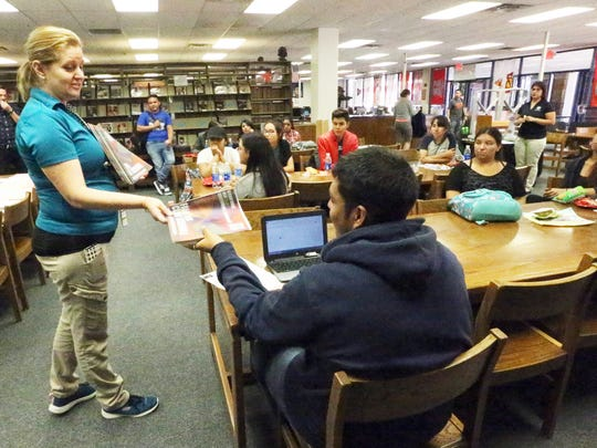 Virginia Madrid, a member of the El Paso Community College Leadership Academy, hands an EPCC course schedule to Bowie High School senior Jose Hernandez during a visit Wednesday to the South El Paso high school. Hernandez is interested in the college's culinary arts program.