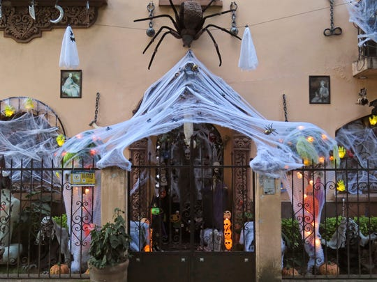 "A large, fake spider and its web cover the entrance of Samuel Soriano's home ahead of Halloween in Mexico City, Friday, Oct. 28, 2016. Soriano and his wife also have a traditional Day of the Dead shrine in their dining room, with portraits of departed loved ones, candles, decorative skulls and marigold flowers. ""We also celebrate Day of the Dead...there's no reason to see it as a contradiction,"" said Soriano."