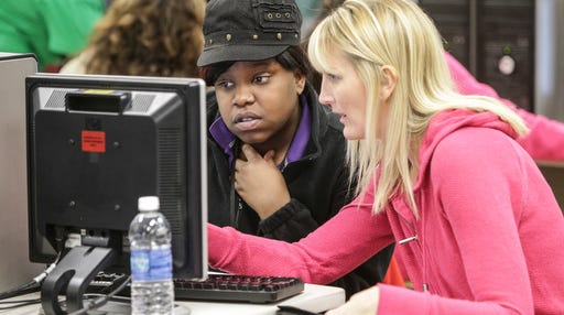 A college-bound student receives help applying for financial aid during a College Goal Sunday event .