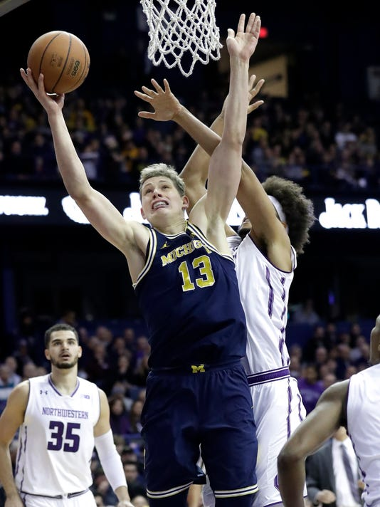 Michigan forward Moritz Wagner, left, drives to the basket against Northwestern center Barret Benson during the first half of an NCAA college basketball game Tuesday, Feb. 6, 2018, in Rosemont, Ill. (AP Photo/Nam Y. Huh)