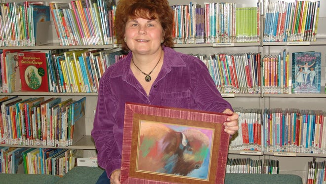 Christy Mosier holds painting of a buffalo. It's one of her favorites and an example of what she calls wild realistic style.