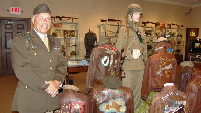 Bill Given, dressed in a World War II 82nd Airborne uniform, poses by a display of A-2 jackets that are part of the exhibit at the Johnson-Humrickhouse Museum.