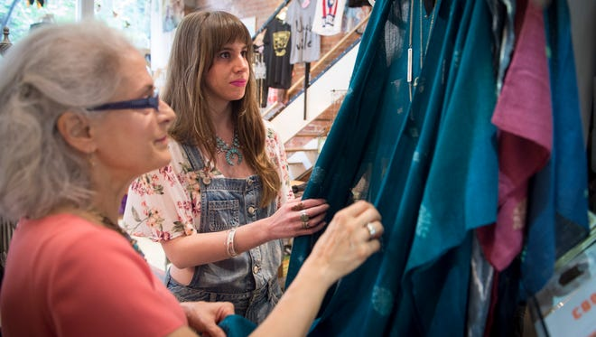 Red Finch employee Jenna Small, center, helps Anne Marie Kempf, left, of Nashville, shop at Fire Finch, Thursday, June 2, 2016, in Nashville, Tenn.