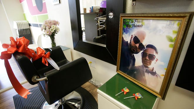 A photo of Pulse nightclub shooting victims Luis Daniel Conde, left, and Juan Rivera Velazquez rests on a shelf near the chair that Velazquez styled hair, at the D'Magazine Salon, Thursday, Dec. 8, 2016, in Orlando, Fla. Jessica Silva, Velazquez's sister in re-opening the salon to honor her brother.