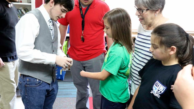 Noah Pittman, left, presents Eden Watts with her new 3D printed hand. What began as a child's request to make a hand for Watts became a reality through the efforts of a team of students and teachers using 3D technology.